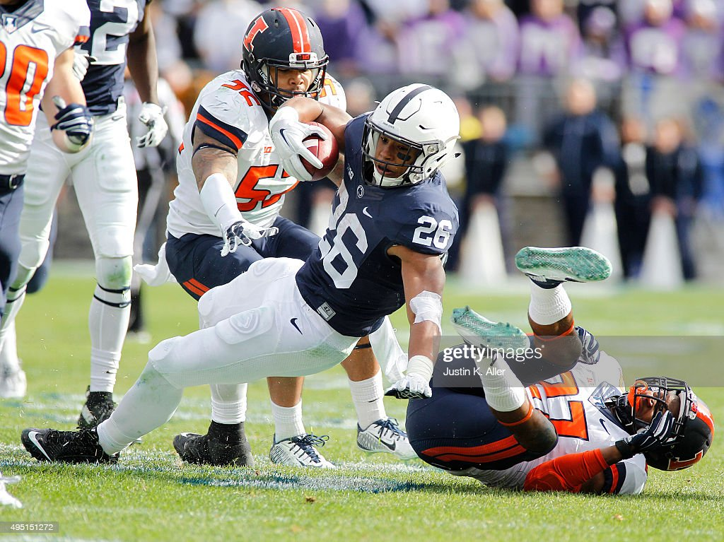 Saquon Barkley #26 of the Penn State Nittany Lions rushes against Eaton Spence #27 of the Illinois Fighting Illini and T.J. Neal #52 in the second half during the game on October 31, 2015 at Beaver Stadium in State College, Pennsylvania.