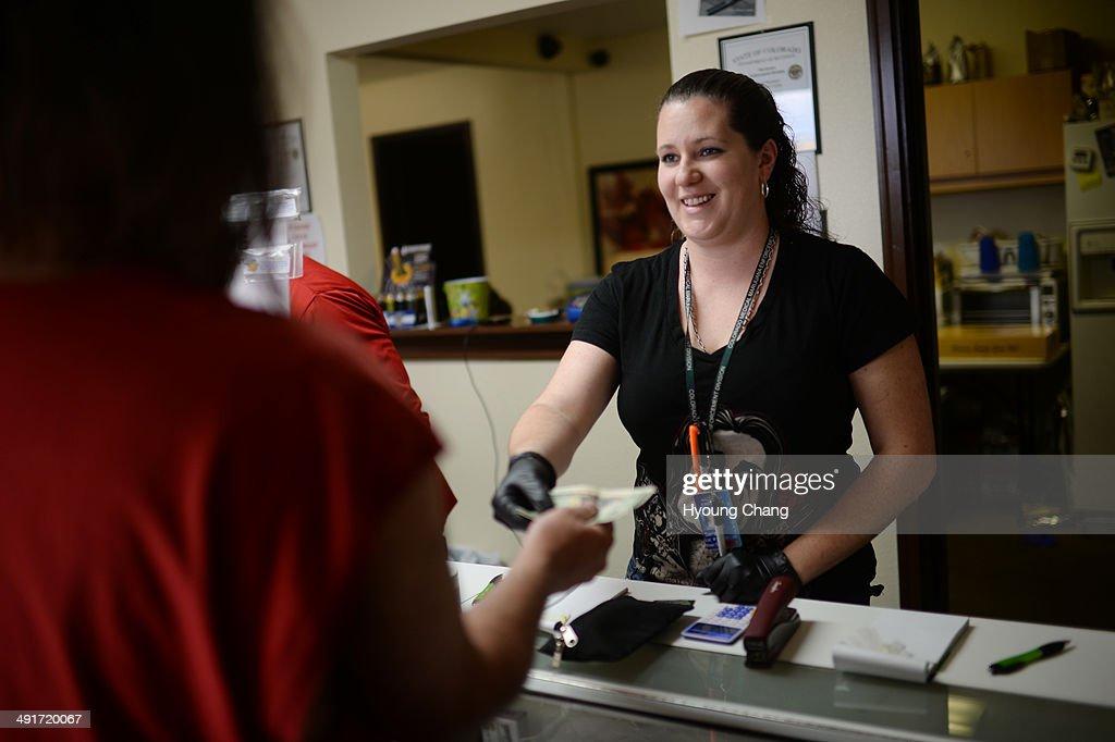 Sara Arbogast of Botana Care, left, helps customers purchasing recreational marijuana. Northglenn, Colorado. May 16. 2014.