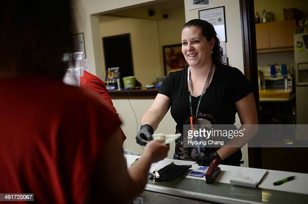 Sara Arbogast of Botana Care left helps customers purchasing recreational marijuana Northglenn Colorado May 16 2014