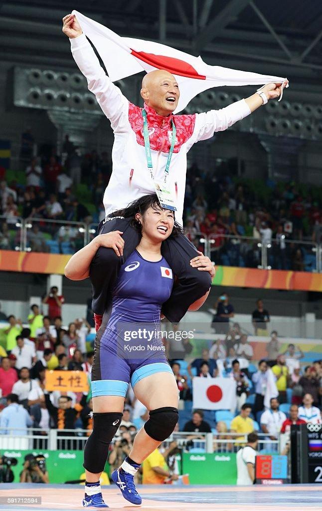 Sara Dosho of Japan carries team director Kazuhito Sakae on her shoulders after winning gold in the women's 69kilogram final in women's wrestling at...