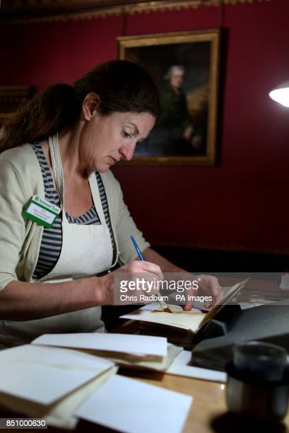 Sara LennoxCook a Paper Conservator works on a collection of water stained books in the Red room at The National Trust's Wimpole Hall in...