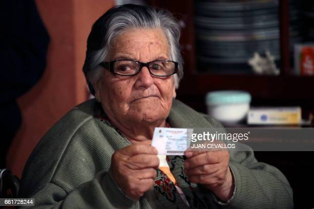 Sara Montenegro shows her voting certificate after casting his vote for Ecuador's presidential runoff at her house in the framework of the 'Vote at...