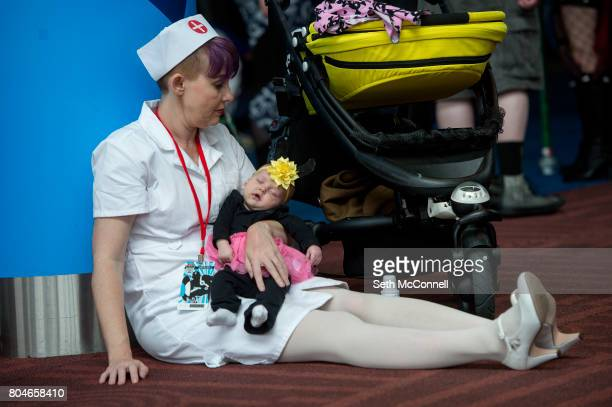Sara Stewart holds her daughter River Stewart 8 weeks dressed as Dot and Hello Nurse from Animaniacs as they take a break during the first day of...