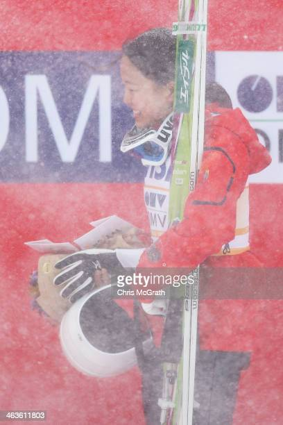 Sara Takanashi of Japan shields herself from a sudden snow gust during the victory ceremony after the Normal Hill Individual Final Round during the...