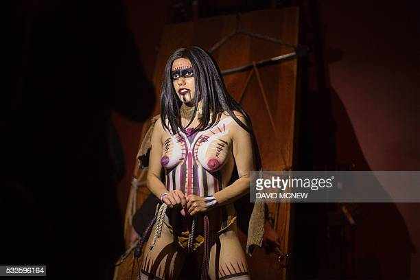 Sara Tonin is illuminated by the light of a smart phone at a dungeon party during the DomCon LA domination convention on May 21 2016 in Los Angeles...