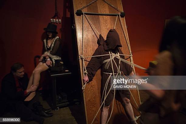 Sara Tonin ties up a voluntary submissive man at a dungeon party during the DomCon LA domination convention on May 21 2016 in Los Angeles California...