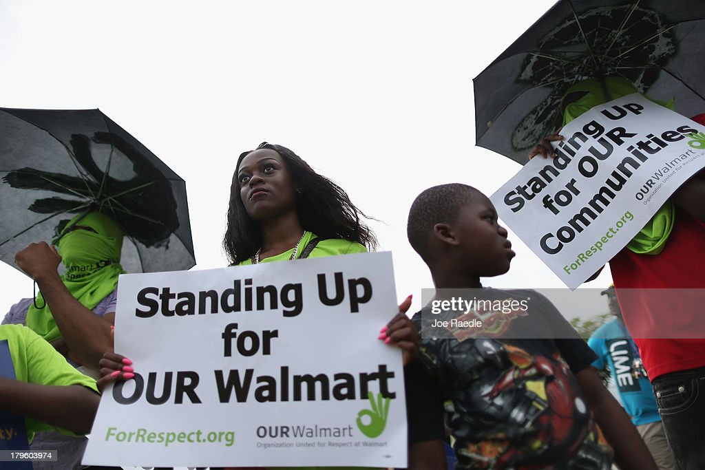 Sarabine Milien (L) and her nephew, Isiaha Chery, join with other protesters in front of a Walmart store as they target the company which they say needs to improve working conditions and rehire workers they say were fired for engaging in labor activities on September 5, 2013 in Miami Gardens, Florida. The protesters joined with others across the nation during a day of action against the company.