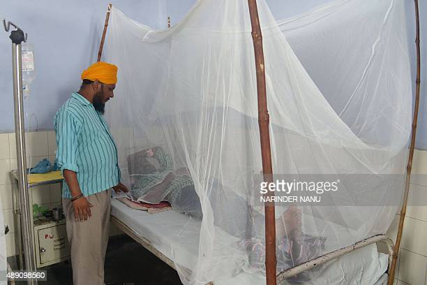 Sarabjit Singh speaks to relative Punjab Singh suffering from dengue as he lays on a bed covered with a mosquito net in the dengue ward of a civil...