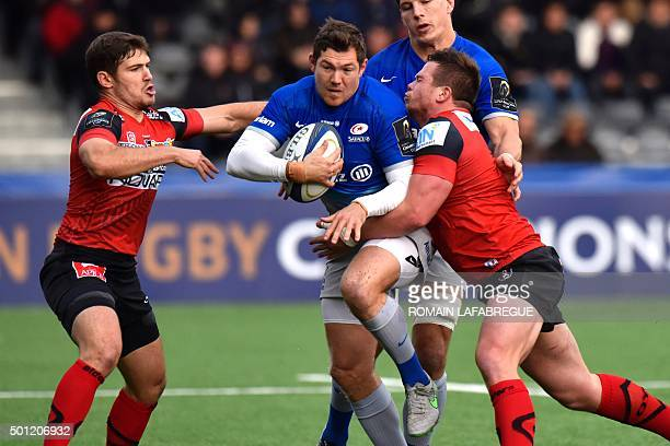 Saracens' English fullback Alex Goode tries to fend off the tackle of Oyonnax' French hooker Thomas Bordes and Oyonnax French scrumhalf Fabien Cibray...