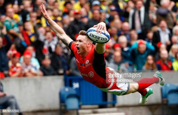 Saracens' English wing Chris Ashton dives over the try line to score the opening try during the rugby union European Champions Cup Final match...
