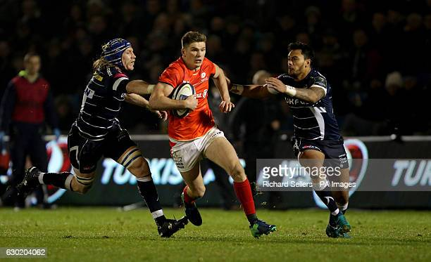 Saracens Owen Farrell sprints past Sale Sharks Magnus Lund and Sale Sharks Denny Solomona during the European Champions Cup pool three mach at the AJ...