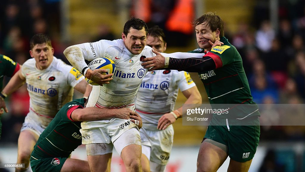 Saracens player Alex Goode hands of Matthew Tait of the Tigers during the Aviva Premiership match between Leicester Tigers and Saracens at Welford...
