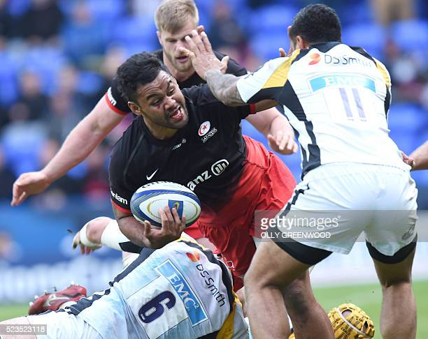 Saracens' prop Billy Vunipola is tackled by Wasps' flanker James Haskell and Wasps' Tongan wing Frank Halai during the European Rugby Champions Cup...
