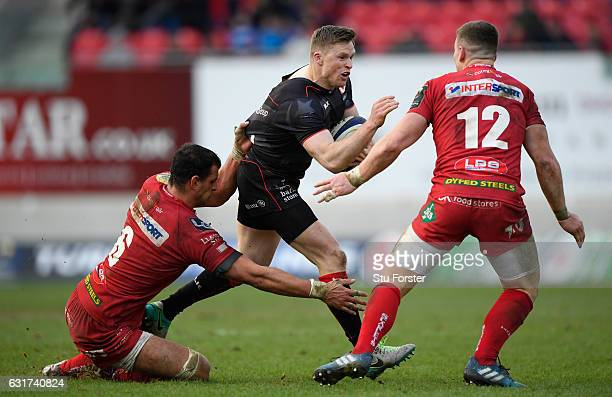 Saracens wing Chris Ashton breaks through the tackle of Aaron Shingler and Scott Williams of the Scarlets during the European Rugby Champions Cup...