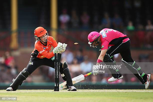 Sarah Aley of the Sixers slides in to avoid a runout as Emily Smith of the Scorchers keeps wicket during the Women's Big Bash League match between...