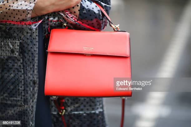 Sarah Benziane fashion blogger wears a Zara blue dress a New Look clear plastic rain coat an Ali Express red bag and Chanel boots with flowers on May...