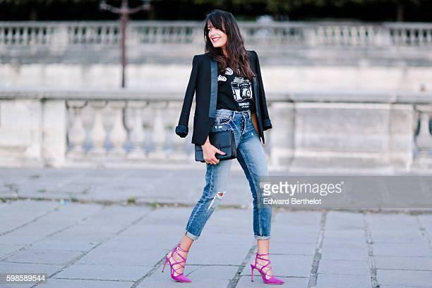 Sarah Benziane is wearing a Vogue Magazine tshirt Mango blue denim ripped jeans pants a Sandro black jacket Zara pink shoes and a Mango black bag at...