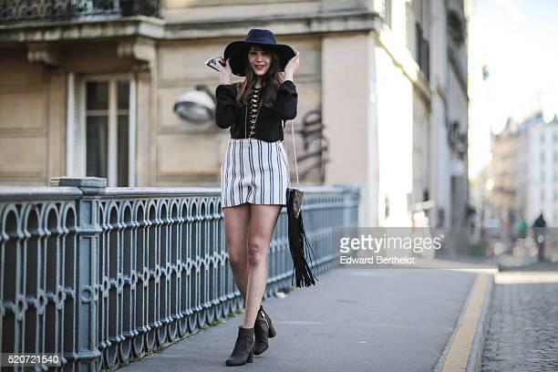 Sarah Benziane is wearing an HM Coachella collection black top a Zara striped short Zara black shoes a Zara black bag and a Zara blue hat during a...
