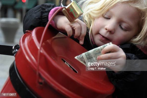Sarah Bicking makes a donation to a Red Kettle on the 16th Street Mall where Salvation Army Bell Ringer Merrill Fie was joined by his grandchildren...