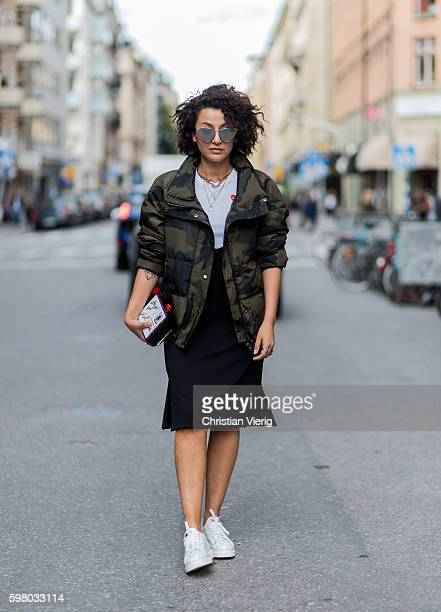 Sarah Che wearing a camouflage jacket and Karl Lagerfeld clutch outside Greta Gram during the second day of the Stockholm Fashion Week Spring/Summer...