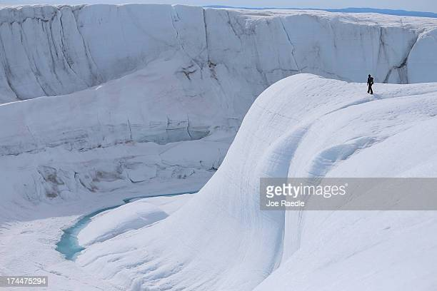 Sarah Das from the Woods Hole Oceanographic Institution looks at a canyon created by a meltwater stream on July 16 2013 on the Glacial Ice Sheet...