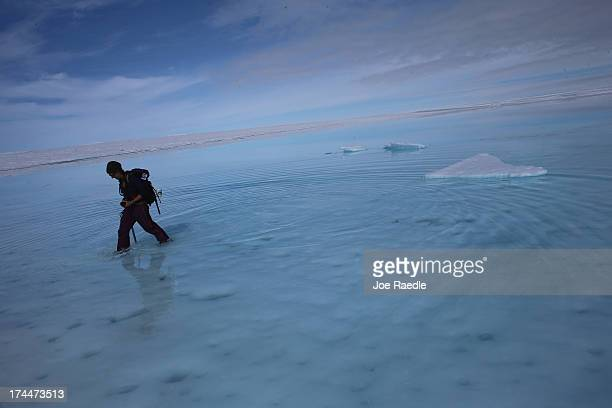 Sarah Das from the Woods Hole Oceanographic Institution walks though a surface meltwater lake on July 16 2013 on the Glacial Ice Sheet Greenland She...