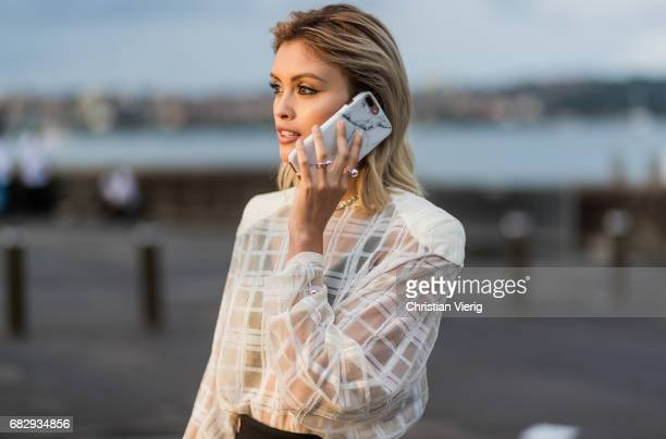 Sarah Ellen on the phone wearing a sheer top outside Dion Lee during MercedesBenz Fashion Week Resort 18 Collections at Sydney Opera House on May 14...