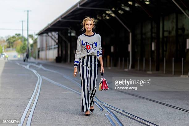 Sarah Ellen wearing a sweater with a Love print from Tommy Hilfiger red black Miu Miu bag and white black striped pants from Daniel Avakian outside C...