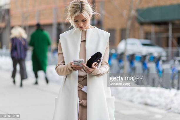 Sarah Ellen wearing a white sleevless coat beige dress Prada clutch outside Dion Lee on February 11 2017 in New York City