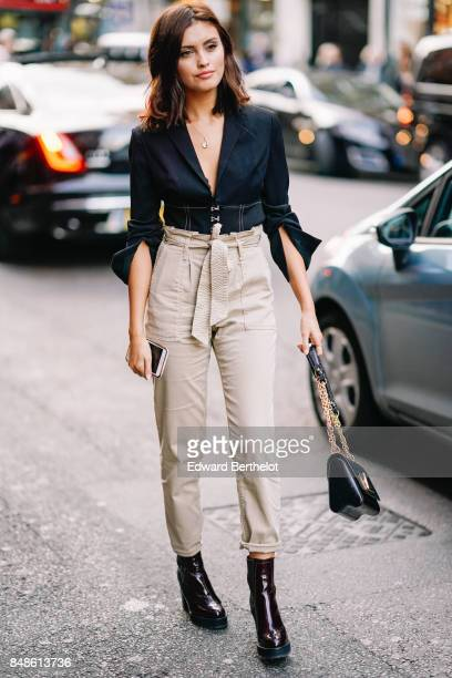 Sarah Ellen wears a black shirt gray pants black shoes a Vuitton bag outside Topshop during London Fashion Week September 2017 on September 17 2017...