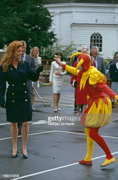 Sarah Ferguson Duchess of York is handed a flower by a man dressed in a jester suit circa 1991