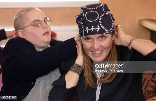 Sarah Ferguson The Duchess of York gets help from Shelly Brocklehurst as she wears a Bandana in support of teenage Cancer victims during her visit to...