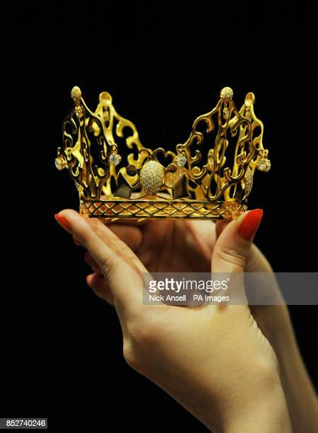 Sarah Gubbins of Bonhams central London with the gold and diamond crown tiara entitled 'East of Paris' worn by Victoria Beckham for her marriage to...