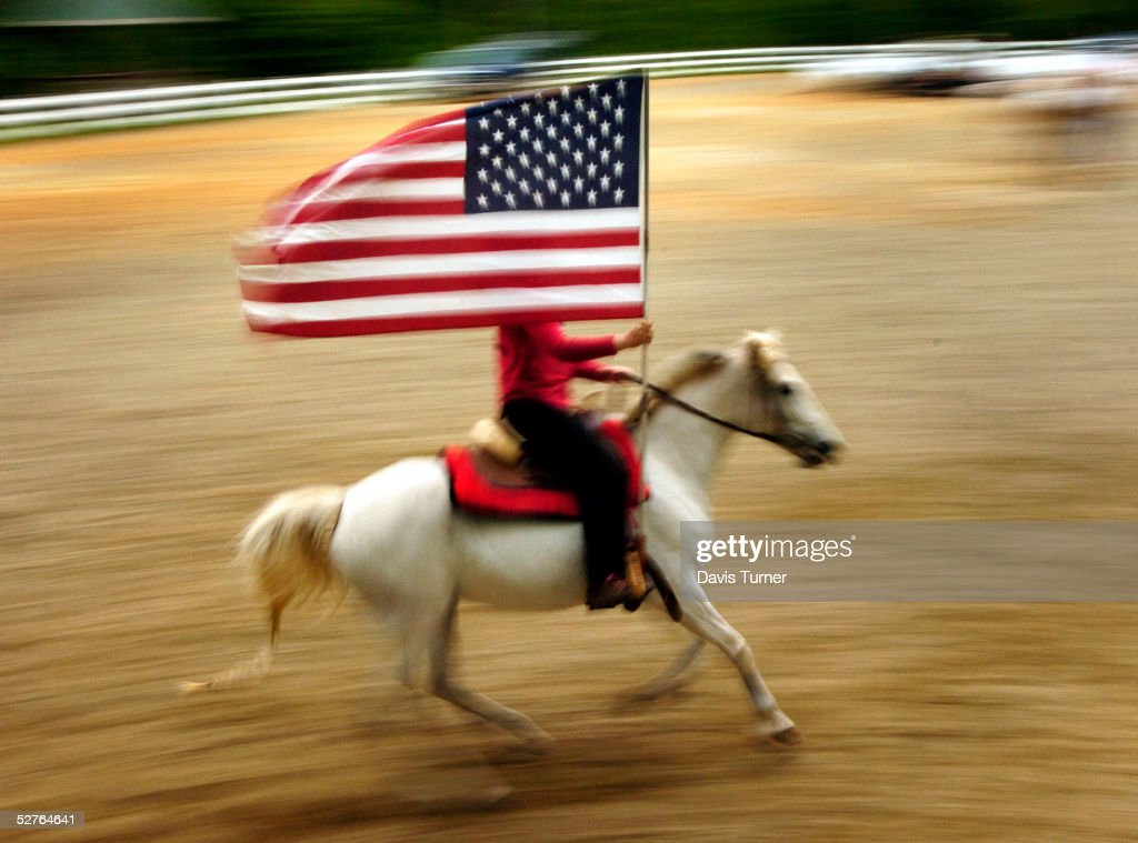 Sarah Harper rides 'Fandango Mist' as she practices presenting the American flag before services May 5, 2005 at the Carolina Cowboy Church in Midland, North Carolina. The church, the eleventh in the Cowboy Church Network, held its first service in a riding ring at Southern Winds Equestrian Center with live music and pony rides following the services.