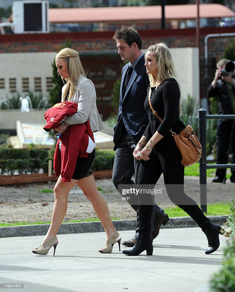 Sarah Harper (L), the girlfriend of Australian baseball player Chris Lane, who was killed in the small Oklahoma town of Duncan in the US, arrives at St Therese's Parish to attend Lane's funeral in Melbourne on August 28, 2013. Lane, 22, was in the US on a baseball scholarship and was jogging in Duncan when he was shot in the back and left to die on the side of the road on August 16. Two teenagers, aged 15 and 16, have been accused of shooting Lane, while a third, aged 17, was charged with use of a vehicle in the discharge of a weapon and acting as an accessory after the fact. AFP PHOTO / Mal Fairclough
