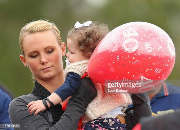 Sarah Harper the girlfriend of Christopher Lane holds Chris's niece Amelia as she releases a balloon to celebrate Lane's life during the Chris Lane...