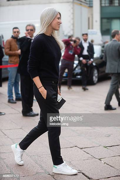Sarah Harris of Vogue UK enters Ferragamo in a Balmain jumper Gucci trousers and Adidas Stan Smith sneakers on Day 5 of Milan Fashion Week FW15 on...