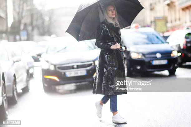 Sarah Harris wears a black vinyl trench coat blue denim jeans white sneakers and an umbrella outside the Valentino show during Paris Fashion Week...