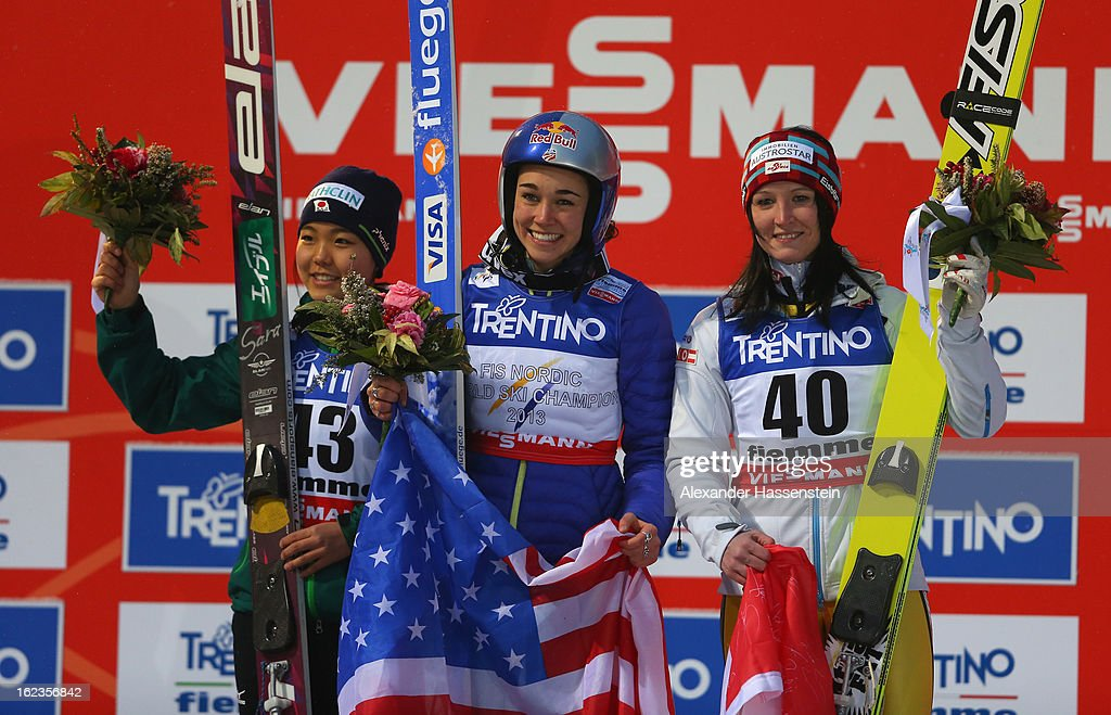 Sarah Hendrickson of the United States poses on the podium following her victory with second placed Sara Takanashi of Japan and third placed...