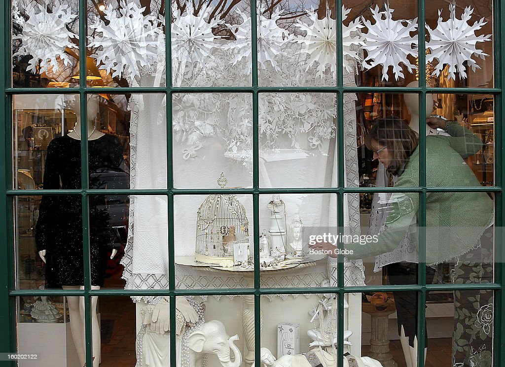 Sarah Horne Gillum puts the finishing touches on a front window display at Vis-A-Vis on Nantucket.