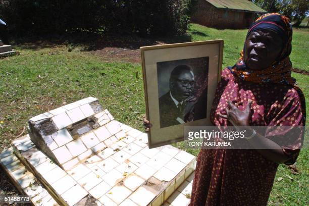Sarah Obama holds a portrait picture of her son Barack Hussein Obama as she stands besides the grave of the belated father of US Senate candidate for...