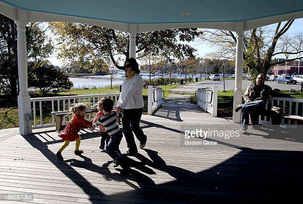 Sarah Pierce leads her daughter and friends playing RingAroundtheRosie on the bandstand at Masconomet Park