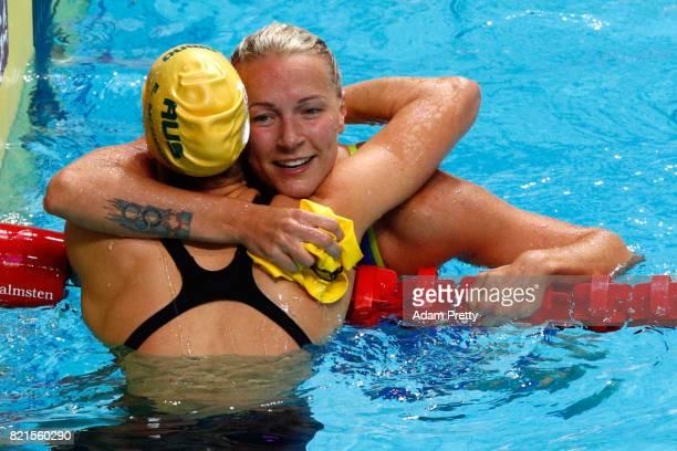 Sarah Sjostrom of Sweden celebrates winning gold with silver medel winner Emma Mckeon of Australia following the Women's 100m Butterfly Final on day...