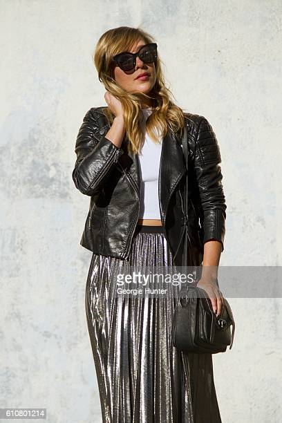 Sarah Stannard wearing sleeveless white HM short ribbed jersey crop top with mock turtleneck Little Mistress lame metallic silver pleated high...