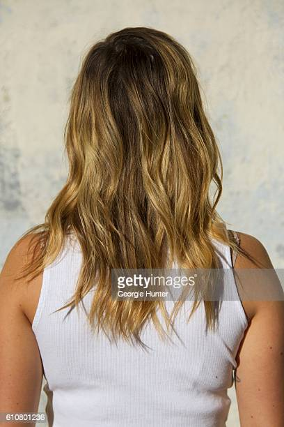 Sarah Stannard wearing sleeveless white HM short ribbed jersey crop top with mock turtleneck with wavy blonde and ash blonde ombre hair with side...