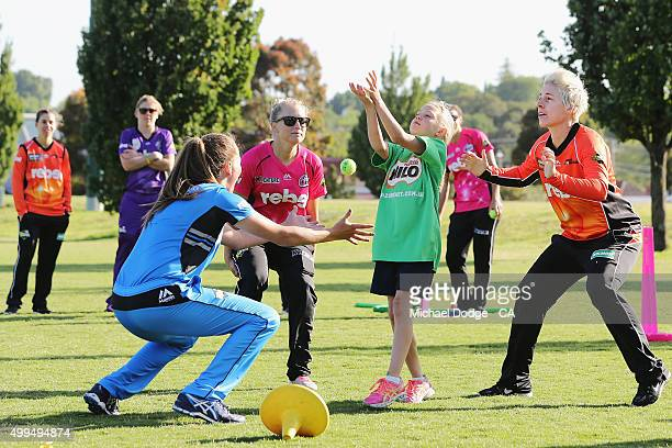 Sarah Taylor of the Adelaide Strikers and Elyse Villani of the Perth Scorchers try to catch a ball with a Milo kid during the Women's Big Bash League...
