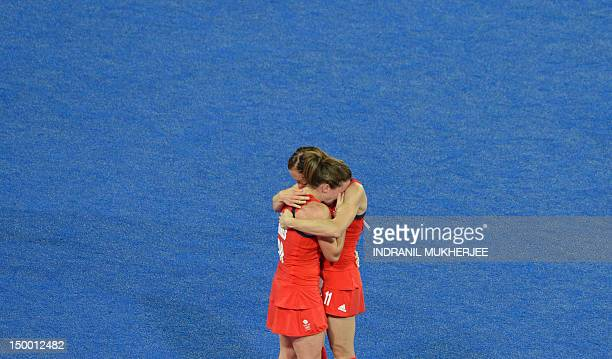 Sarah Thomas of Britain is consoled by captain Kate Walsh after their defeat to Argentina in the second semifinal of the women's field hockey match...