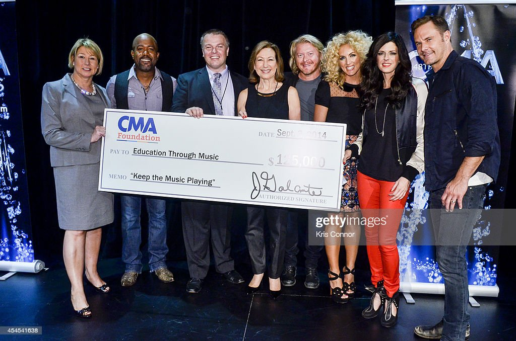 Sarah Trahern, Karen Fairchild, Darius Rucker, Kimberly Schlapman, Jimi Westbrook and Phillip Sweet pose with a check during the 48th Annual CMA Awards Nominees Announcement at Best Buy Theater on September 3, 2014 in New York City.