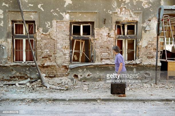 A Sarajevo resident walks past a damaged house in fornt of the french hospital in Sarajevo on August 26 1992 A nurse was killed in the hospital when...