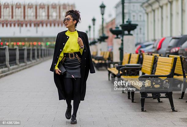 SaraJoleen Kaveh Moghaddam wearing a yellow Zara sweater a black leather skirt Chanel belt Tigha clutch Religion wool coat Dr Martens shoes during...